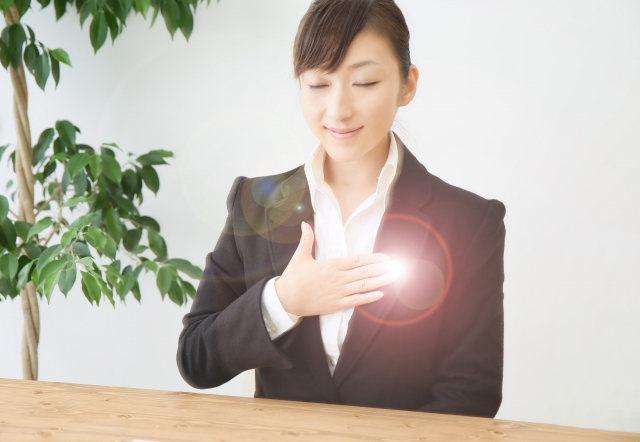 胸に手を当てるスーツの女性